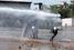 Демонстранты пытаются защитить себя от водометов