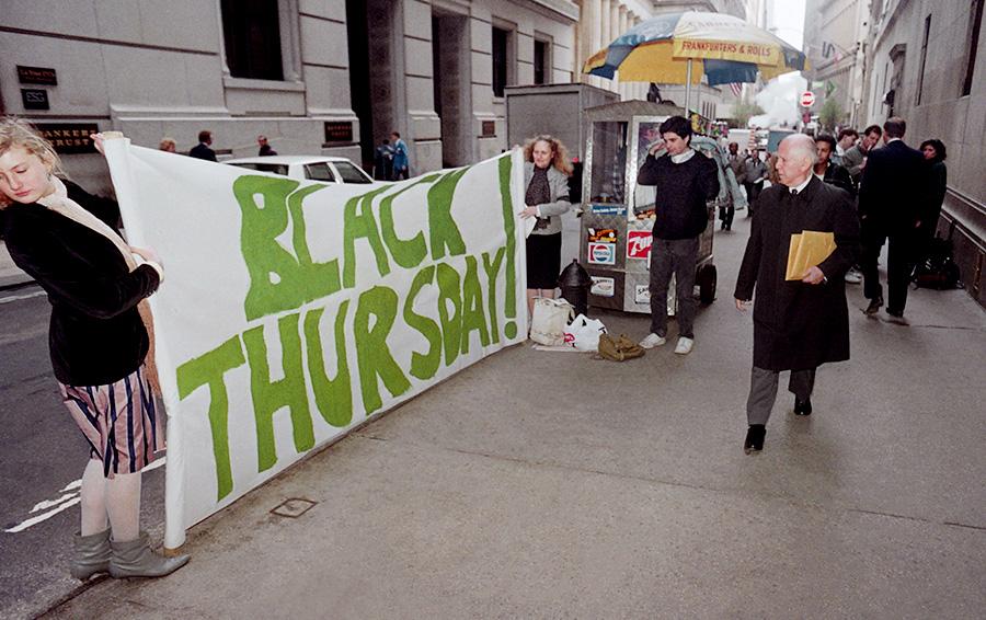 Группа протестующих с плакатом у входа в Нью-Йоркскую фондовую биржу на Уолл-стрит 29 октября 1987 года в 58-ую годовщину краха фондового рынка 1929 года, которая была известна как Черная пятница