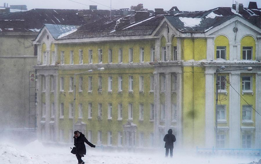 Прохожие на улице Комсомольской во время метели.