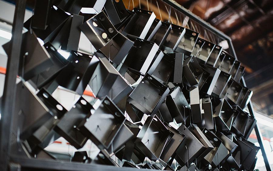 В подвешенном состоянии металлические ящики отправляют в камеру для покраски