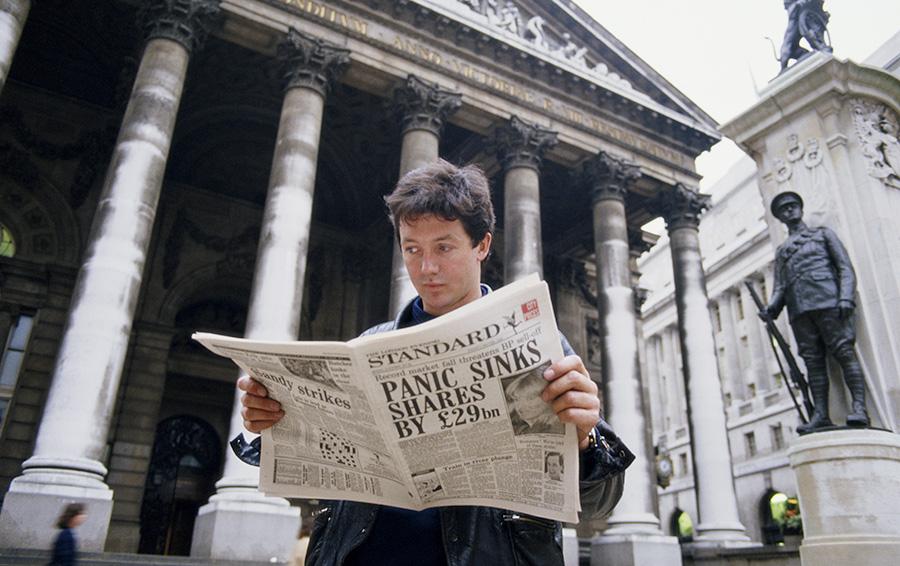 Молодой человек читает газету «Evening Standard» в Лондоне с заголовком, касающимся краха фондового рынка, известного как Черный понедельник, 19 октября 1987 года