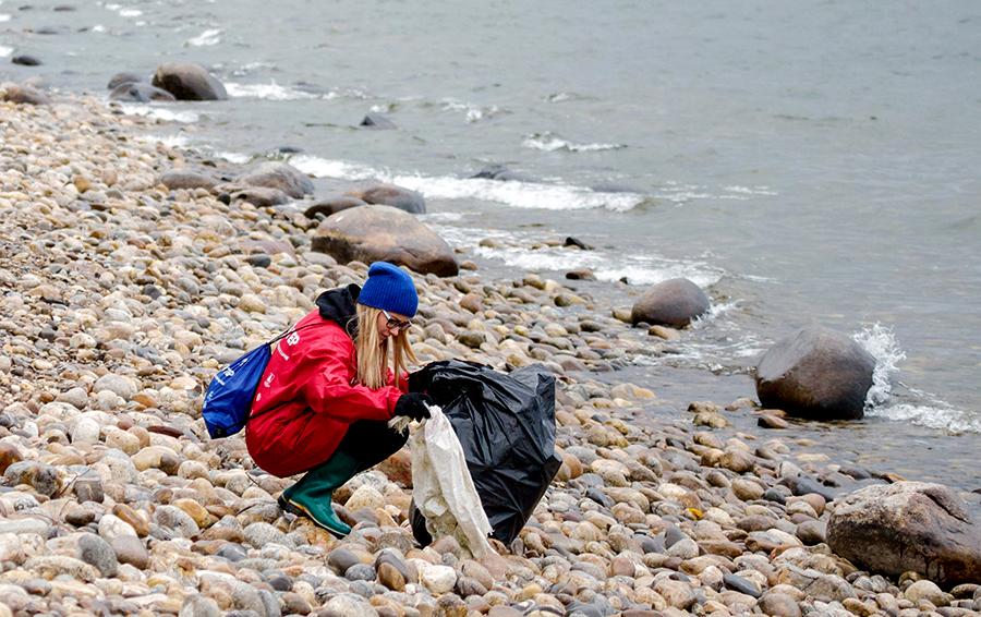 Волонтер во время уборки мусора на берегу озера Байкал